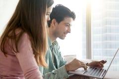Молодые люди ходить по магазинам онлайн через компьтер-книжку, кредитную карточку, взгляд со стороны Стоковые Фото