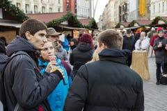 Молодые люди ходя по магазинам на традиционных рождественских ярмарках на Masaryk придает квадратную форму Masarykovo Namesti в Б Стоковые Фотографии RF