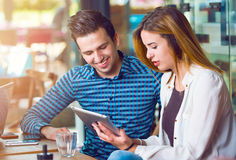 2 молодые люди, человек и женщина, смотря таблетку Стоковое фото RF