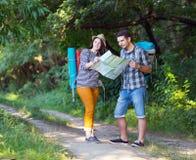 Молодые Hikers смотря в карту на следе леса Стоковые Изображения