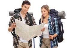 Молодые hikers смотря родовую карту Стоковое Изображение