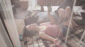 Молодые multiracial пары в пижамах лежа на кровати и слушая музыке Smartphone пользы человека и женщины, танцуя Стоковые Фотографии RF