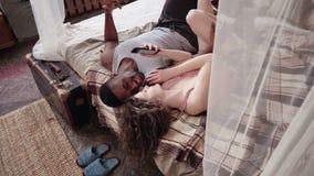 Молодые multiracial пары в пижамах лежа на кровати и слушая музыке Smartphone пользы человека и женщины, танцуя Стоковые Изображения RF