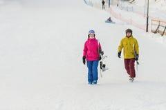 Молодые snowboarders пар идут идти с досками Стоковые Фотографии RF