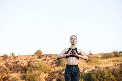 Молодые sportive asanas йоги тренировки девушки на утесе в каньоне Стоковая Фотография