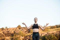 Молодые sportive asanas йоги тренировки девушки на утесе в каньоне Стоковые Фото