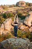 Молодые sportive asanas йоги тренировки девушки на утесе в каньоне Стоковые Фотографии RF