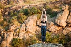 Молодые sportive asanas йоги тренировки девушки на утесе в каньоне Стоковое Изображение RF