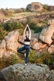 Молодые sportive asanas йоги тренировки девушки на утесе в каньоне Стоковая Фотография RF