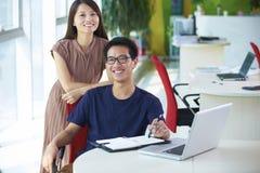 2 молодых азиатских предпринимателя в офисе Стоковые Фото