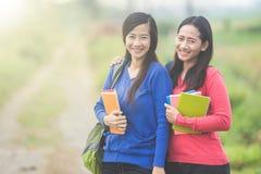 2 молодых азиатских студента держа книги, усмехаясь ярко к Стоковые Изображения