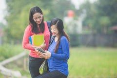 2 молодых азиатских студента держа книги, усмехаясь ярко к Стоковое Изображение