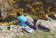 2 молодых дамы на том основании в горе смотря к красивому ландшафту Стоковое фото RF