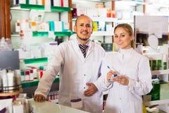 2 молодых аптекаря стоя рядом с полками Стоковая Фотография RF