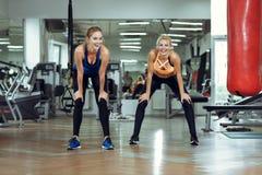 2 молодых атлетических женщины тренируют совместно в спортзале Стоковое фото RF
