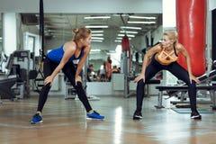 2 молодых атлетических женщины тренируют совместно в спортзале Стоковое Изображение RF