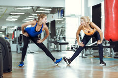 2 молодых атлетических женщины тренируют совместно в спортзале Стоковое Фото