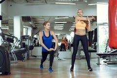 2 молодых атлетических женщины тренируют совместно в спортзале Стоковая Фотография RF