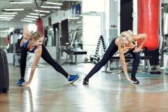 2 молодых атлетических женщины тренируют совместно в спортзале Стоковые Фотографии RF