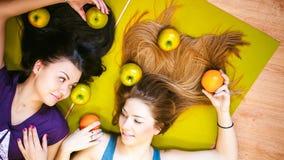2 молодых атлетических женщины физических данных в спортзале лежат на поле на циновках йоги Стоковые Изображения