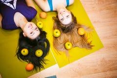 2 молодых атлетических женщины физических данных в спортзале лежат на поле на циновках йоги Стоковая Фотография RF