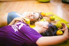 2 молодых атлетических женщины физических данных в спортзале лежат на поле на циновках йоги Стоковое Изображение