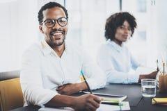 2 молодых африканских бизнесмены работая совместно в современном офисе Чернокожий человек и женщина усмехаясь на камере Стоковые Изображения RF