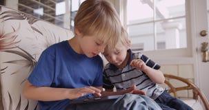 2 молодых белых дет играя с таблеткой Стоковое Фото