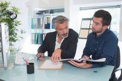 2 молодых бизнесмена говоря в офисе Стоковая Фотография RF