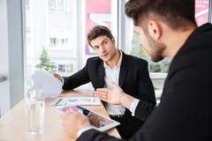 2 молодых бизнесмена обсуждая бизнес-план и используя таблетку Стоковая Фотография