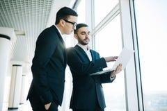 2 молодых бизнесмена обсуждая проект Стоковые Изображения RF