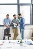 3 молодых бизнесмена стоя совместно и обсуждая бумаги Стоковая Фотография RF