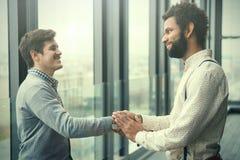 2 молодых бизнесмена тряся руки в современной зале офиса Стоковые Изображения RF