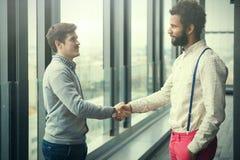 2 молодых бизнесмена тряся руки в современной зале офиса Стоковые Фотографии RF