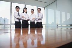 4 молодых бизнесмены готовя стол переговоров, смотря камеру, портрет Стоковая Фотография RF