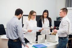 4 молодых бизнесмены работая в команде собрали вокруг портативного компьютера в офисе открытого плана современном Стоковая Фотография RF
