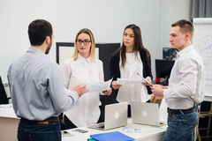 4 молодых бизнесмены работая в команде собрали вокруг портативного компьютера в офисе открытого плана современном Стоковое Изображение
