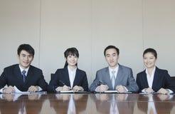 4 молодых бизнесмены сидя в ряд на столе переговоров, портрете Стоковое Изображение