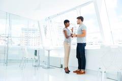 2 молодых бизнесмены стоя и говоря в офисе Стоковые Изображения
