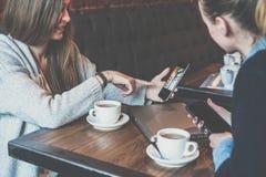 2 молодых бизнес-леди сидя на таблице и используя smartphones Женщина показывая изображение коллеги на экране smartphone Стоковые Фото