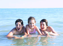 3 молодых брать играя в воде моря Стоковые Фотографии RF