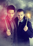 2 молодых волшебника держа волшебную палочку стоковая фотография rf