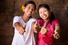 2 молодых девушки Мьянмы давая большой палец руки вверх Стоковое фото RF