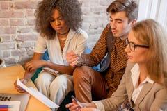 3 молодых делового партнера обсуждая что-то смотря graphigs Одно из их Афро-американская девушка Стоковая Фотография