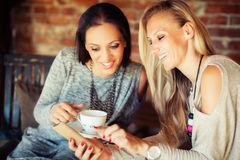 2 молодых женских друз злословя в баре Стоковая Фотография