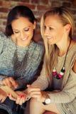 2 молодых женских друз злословя в баре Стоковое Фото