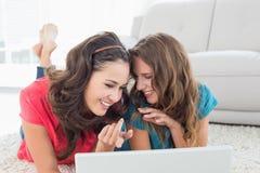 2 молодых женских друз используя компьтер-книжку дома Стоковые Фотографии RF