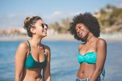 2 молодых женских друз на смеяться над взморья Стоковые Изображения RF