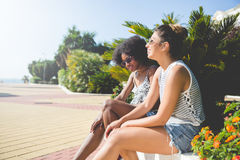 2 молодых женских друз ослабляя снаружи в солнце Стоковые Изображения RF