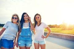 3 молодых женских друз представляя против захода солнца Стоковое Изображение